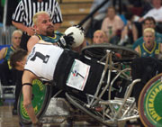 George Hucks of Australia retains the ball as Timothy Johnson of New Zealand falls from his wheelchair during the Rugby Wheelchair semi final game at the 2000 Paralympic Games in Sydney. © Scott Barbour/Allsport